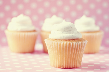 Four cupcakes on polka dot background Banco de Imagens
