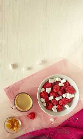 Sweet raspberrys with marshmallow and hot coffee for tasty morning meals. Delicious start of the day. Concept of healthy food without carbohydrates, keto diet. Top view, copy space on natural wood
