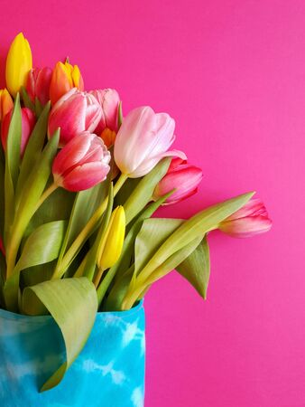 Spring holiday bouquet for Womens Day. Flowers in eco-friendly textile packaging. Concept without plastic. Multi-colored tulips in a woven bag on a pink background. Vertical orientation