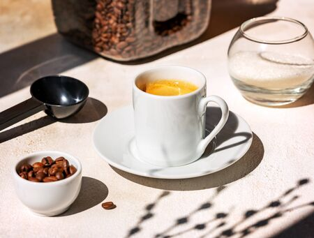 Fresh delicious espresso, a Cup of hot coffee with coffee beans and sugar on a light background with contrasting shadows