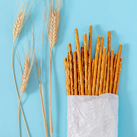 Flour snack. Salted, baked, wheat sticks in a bag made of white ecological paper with wheat spikelets on a blue background. Bread festival. Concept of natural products .Food photos, top view