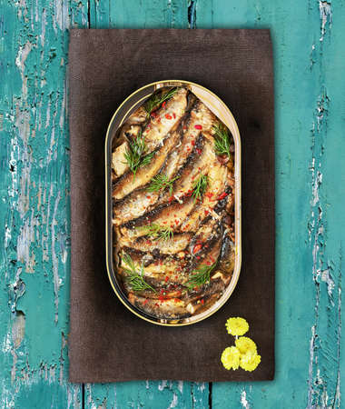 Open tin of Baltic sprats in oil with spices on an old blue wooden background Reklamní fotografie