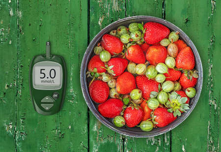Fresh natural strawberries and gooseberries in a bowl with a glucose meter with a good glucose indicator 版權商用圖片