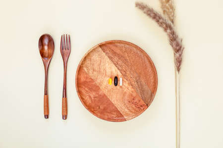 Immunity boosting vitamins. Eco friendly, health care, minimalistic composition with three different capsules on a wooden plate with wooden spoon, fork and dry flowers on a white background