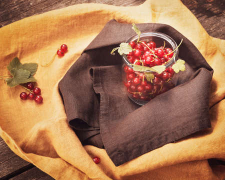 Food, summer composition with organic red currants in a glass jar on a textile background. Eco friendly, mindful eating. Immune boosting food, natural remedy for immunity Stock fotó