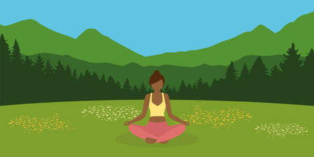 sporty girl makes yoga on a summer meadow with mountain landscape