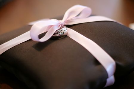 bearer: brown ring bearer pillow with a pink ribbon