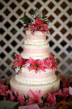 a wedding cake wrapped in pink ribbon and topped with lilies on a table with a white lattice backdrop photo