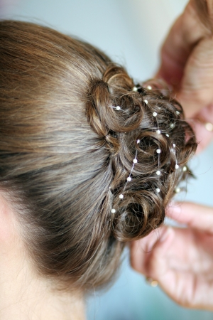 curls: a woman getting her hair styled for a wedding with curls and pearls
