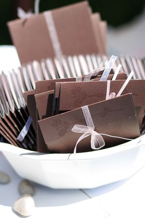 favor: brown and pink wedding programs organized neatly in a bowl for the guests