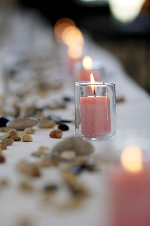decoration: a row of pink candles in votives decorate a wedding reception table sprinkled with stones and pebbles Stock Photo