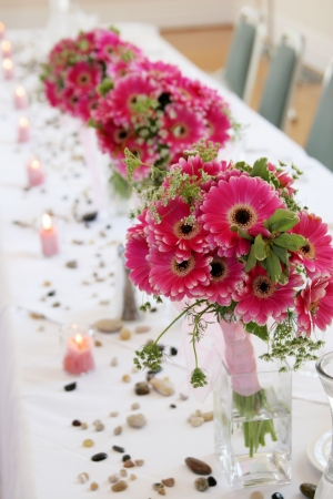pink daisy bouquets in vases decorate a wedding reception table