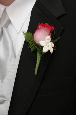 Groom in tuxedo with red and white rose boutonniere Stock Photo