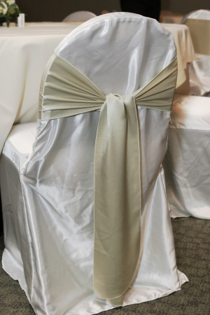 Wedding reception chair covered in white satin with a gold sash photo