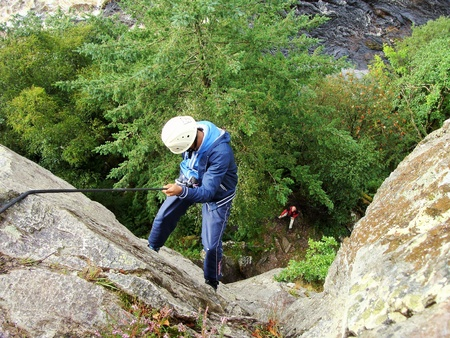 abseiling: A young man is abseiling down a vertical Rock face