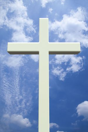 White Christian cross in front of a cloudy sky Stock Photo
