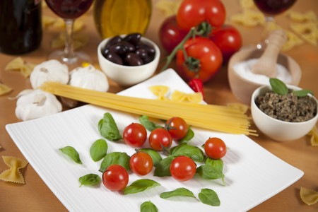 Basil and cherry tomatoes on a plate surrounded by some ingredients photo