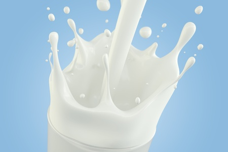 Splashing milk in a glass on a light blue background photo