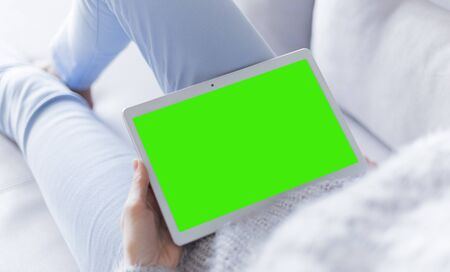 Woman at home relaxing reading on the tablet computer with pre-keyed green screen