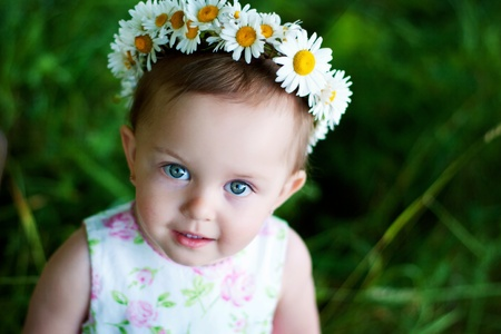 Little girl with wreath from daisies Stock Photo