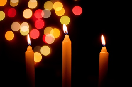 burning candles with defocussed Christmas lights behind Stock Photo - 9236035