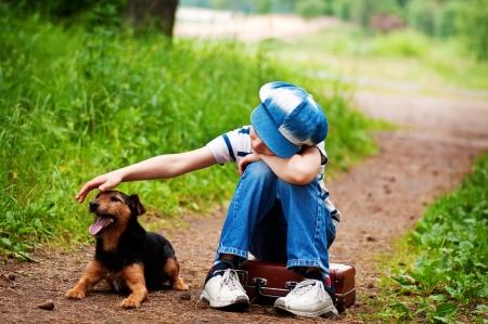 De jongen met zijn hond in het bos