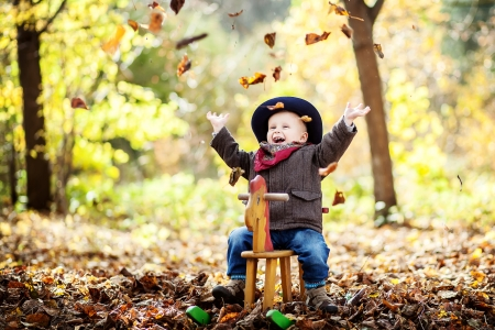 little boy on the wooden rocking horse in the autumn forest