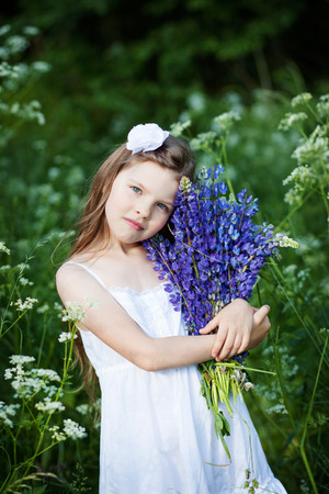 lupines: Beautiful little girl with purple lupines outdoors