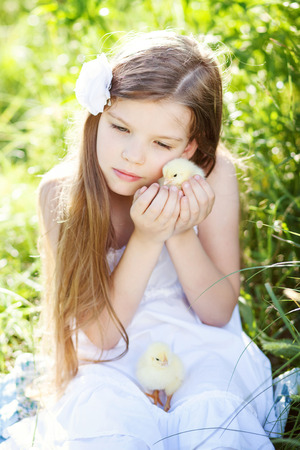 cute girl with little chicken outdoors