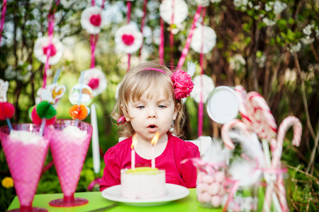 little girl is blowing birthday candles