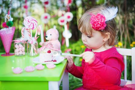 little girl is eating cake