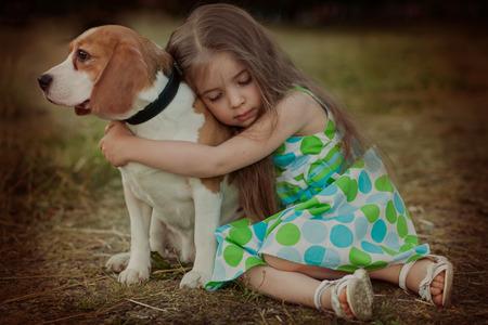 little girl holding dog outdoors