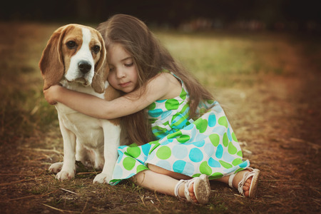 little girl is holding dog outdoors