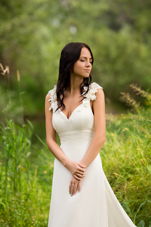 slinky: Portrait of a beautiful young bride wearing a slinky dress in the foliar summer forest