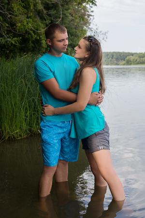 강물에 서있는 동안 키스하는 젊은 부부