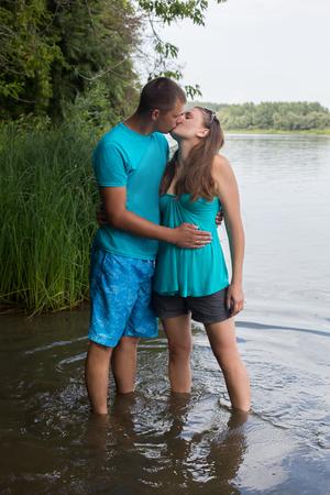 젊은 부부는 물에 서있는 동안 키스 스톡 콘텐츠