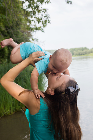 Mom raises over a little boy on the riverbank