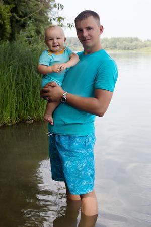 젊은 아버지는 강둑에 그녀의 팔에 아기 아들을 보유하고 스톡 콘텐츠