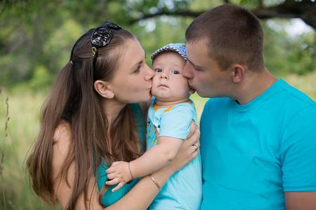 어머니, 아버지와 작은 아들 아름 다운 초원에 나무 아래 서. 행복한 가정. 부모와 자식