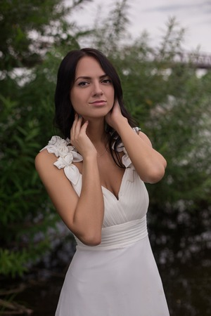 어두운 피부, 검은 머리 소녀 연못 근처 흰 드레스에. 아름 다운 젊은 신부 강둑에