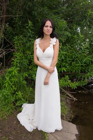 어두운 피부, 검은 머리 소녀 연못 근처 흰 드레스에. 강둑에 아름다운 신부