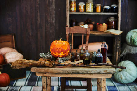 hallowen: Old wooden table, orange hallowen pumpkin, dried herbs and bottles, a top view, in the studio, in the afternoon.