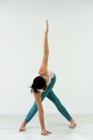 beautiful girl in blue pants and white t-shirt doing yoga in Studio on white background.