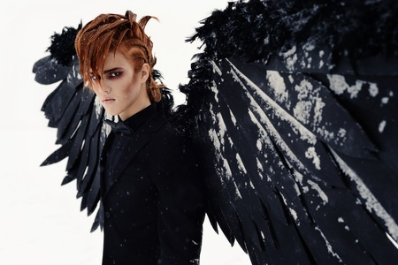 a cute man with red hair , a black angel on the lake, white snow