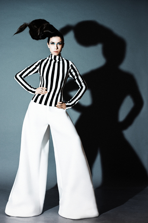 the girl in the wide white pants and striped jacket posing on grey background