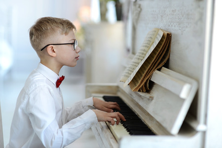 elegant boy in white shirt and glasses plays the piano