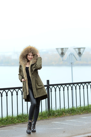 a girl in a green jacket with a fur collar in glasses posing near the lake