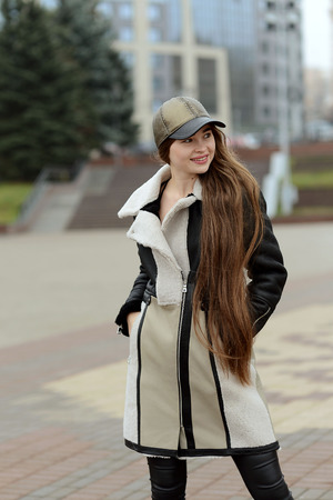 a girl in a black leather jacket and beige skirt in a cap posing in the city square