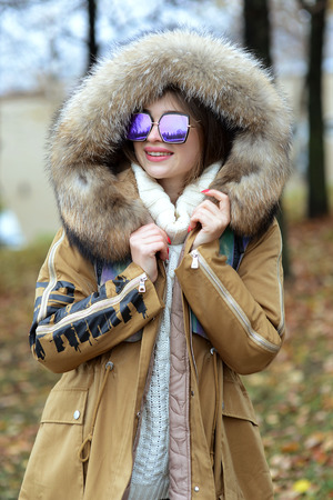 girl in a down jacket with fur and blue glasses walking in the woods