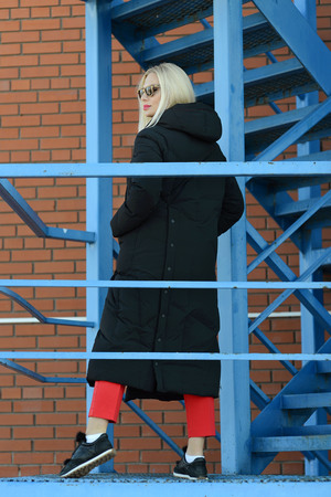 girl in coat posing on an urban staircase
